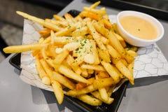Οι τηγανιτές πατάτες με το τυρί σκονών και τη σάλτσα μαγιονέζας εξυπηρετούν στο μαύρο πιάτο για το υπόβαθρο τροφίμων Στοκ Φωτογραφίες