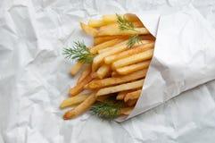 Οι τηγανιτές πατάτες πατατών στη Λευκή Βίβλο τοποθετούν σε σάκκο σε ένα φύλλο του ελαφριού π Στοκ Εικόνες