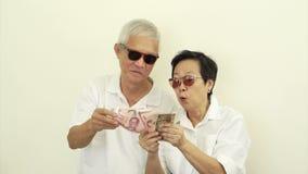 Οι τηλεοπτικοί ευτυχείς πλούσιοι δροσίζουν τον ασιατικό πρεσβύτερο με το μέρος των χρημάτων μετρητών Ρίψη των χρημάτων στον αέρα φιλμ μικρού μήκους