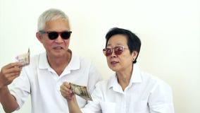 Οι τηλεοπτικοί ευτυχείς πλούσιοι δροσίζουν τον ασιατικό πρεσβύτερο με το μέρος των χρημάτων μετρητών Ρίψη των χρημάτων στον αέρα απόθεμα βίντεο