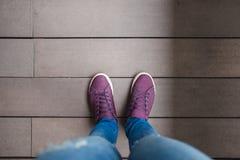 Οι τοπ γυναίκες ποδιών άποψης με Jean και το παπούτσι στέκονται στην ξύλινη ΤΣΕ πατωμάτων στοκ εικόνα με δικαίωμα ελεύθερης χρήσης