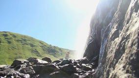 Οι τουρίστες απολαμβάνουν τη φρεσκάδα του νερού καταρρακτών, τοπίο βουνών απόθεμα βίντεο