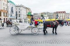 Οι τουρίστες απολαμβάνουν έναν γύρο μεταφορών στο τετράγωνο αγοράς στην Κρακοβία Στοκ εικόνα με δικαίωμα ελεύθερης χρήσης