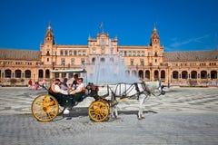 Οι τουρίστες απολαμβάνουν ένα ταξίδι στο horsedrawn κάρρο Plaza de Espana, Sev Στοκ Φωτογραφίες