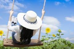 Οι τουρίστες γυναικών απολαμβάνουν την όμορφη φύση, παίζουν την ξύλινη ταλάντευση στοκ εικόνες
