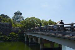 Οι τουρίστες διασχίζουν τη γέφυρα στην Οζάκα Castle στοκ εικόνες με δικαίωμα ελεύθερης χρήσης