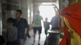 Οι τουρίστες κινούνται κοντά στο γλυπτό του Βούδα στην Ταϊλάνδη στο βουδιστικό ναό απόθεμα βίντεο