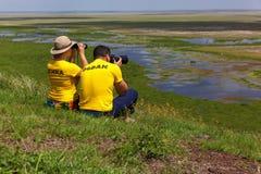 Οι τουρίστες κοιτάζουν και παίρνουν το τοπίο εικόνων σε Amboseli εθνικό Π Στοκ εικόνα με δικαίωμα ελεύθερης χρήσης