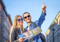 Οι τουρίστες με την πόλη χαρτογραφούν Στοκ εικόνες με δικαίωμα ελεύθερης χρήσης