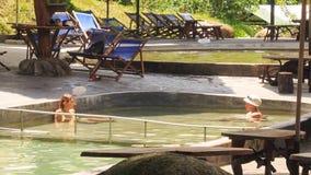 Οι τουρίστες λούζουν στις ειδικές ιατρικές θερμές λίμνες στο πάρκο τουριστών απόθεμα βίντεο