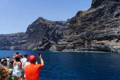 Οι τουρίστες παίρνουν τις εικόνες των κάθετων απότομων βράχων Acantilados de Los Gigantes Cliffs των γιγάντων στοκ εικόνα