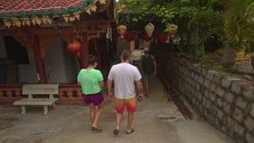 Οι τουρίστες περπατούν γύρω από το βουδιστικό ναό κάτω από τα κινεζικά φανάρια απόθεμα βίντεο