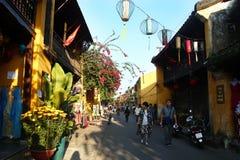Οι τουρίστες περπατούν σε μια οδό του παλαιού ιστορικού κέντρου Hoi με τα κίτρινα κτήρια, τα καταστήματα και τα ζωηρόχρωμα κινεζι στοκ εικόνες με δικαίωμα ελεύθερης χρήσης