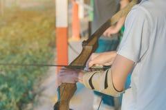 Οι τουρίστες προσπαθούν να χρησιμοποιήσουν ένα τόξο και ένα βέλος και το βλαστό σε έναν στόχο στοκ εικόνες