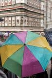 Οι τουρίστες προφυλάσσουν κάτω από τις ζωηρόχρωμες ομπρέλες Στοκ Εικόνες