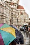 Οι τουρίστες προφυλάσσουν κάτω από τις ζωηρόχρωμες ομπρέλες Στοκ Εικόνα