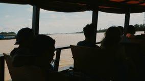 Οι τουρίστες σε μια μηχανοποιημένη ξύλινη βάρκα πλέουν κατά μήκος του ποταμού Μεκόνγκ απόθεμα βίντεο