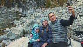 Οι τουρίστες στηρίζονται μετά από το πεζοπορώ και παίρνουν selfie στο τηλέφωνο οικογενειακά ταξίδια Περιβάλλον ανθρώπων από τους  φιλμ μικρού μήκους