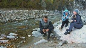 Οι τουρίστες στρατοπεδεύουν κοντά στον ποταμό Καυστήρας σομπών στρατόπεδων εγκατάστασης Καύσιμα προπανίου, αντιστοιχίες στρατόπεδ απόθεμα βίντεο