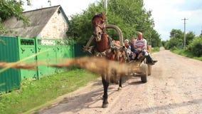Οι του χωριού άνθρωποι οδηγούν στο κάρρο αλόγων, θερινή ημέρα, φτωχοί χωρικοί απόθεμα βίντεο