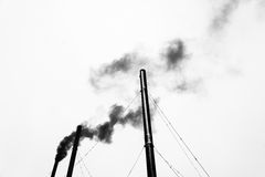 Οι τρεις μαύροι σωλήνες και ο μαύρος καπνός σε ένα ανοικτό γκρι υπόβαθρο Στοκ Φωτογραφία