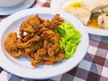 Οι τριζάτες τηγανισμένες λουρίδες χοιρινού κρέατος σε ένα άσπρο πιάτο διακοσμούν με το πράσινο μαρούλι στοκ φωτογραφίες με δικαίωμα ελεύθερης χρήσης
