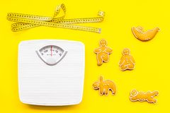 Οι τρόποι για χάνουν το βάρος αθλητισμός Μπισκότα στη μορφή της γιόγκας asans κοντά στην κλίμακα και μέτρηση της ταινίας στο φωτε Στοκ Εικόνα