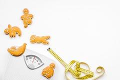 Οι τρόποι για χάνουν το βάρος αθλητισμός Μπισκότα στη μορφή της γιόγκας asans κοντά στην κλίμακα και μέτρηση της ταινίας στην άσπ Στοκ Εικόνα