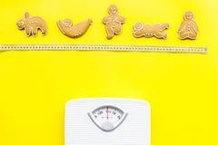 Οι τρόποι για χάνουν το βάρος αθλητισμός Μπισκότα στη μορφή της γιόγκας asans κοντά στην κλίμακα και μέτρηση της ταινίας στο φωτε Στοκ Εικόνες