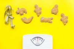 Οι τρόποι για χάνουν το βάρος αθλητισμός Μπισκότα στη μορφή της γιόγκας asans κοντά στην κλίμακα και μέτρηση της ταινίας στο φωτε Στοκ εικόνες με δικαίωμα ελεύθερης χρήσης