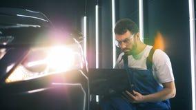 Οι τύποι εργαζομένων υπηρεσιών σε ένα lap-top, κλείνουν επάνω Επισκευαστής που καθορίζει ένα αυτοκίνητο Έννοια υπηρεσιών αυτοκινή απόθεμα βίντεο