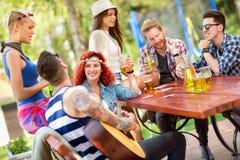 Οι τύποι και lassies περνούν την ηλιόλουστη ημέρα σε ανοικτό με τα ποτά και την κιθάρα Στοκ Εικόνες