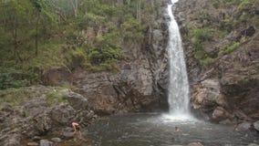 Οι τύποι κολυμπούν από τον υψηλό καταρράκτη στον ποταμό στο τροπικό πάρκο απόθεμα βίντεο