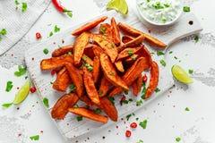 Οι υγιείς σπιτικές ψημένες πορτοκαλιές σφήνες γλυκών πατατών με τη φρέσκια κρέμα βυθίζουν τη σάλτσα, τα χορτάρια, το αλάτι και το στοκ εικόνα