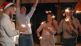 Οι υπάλληλοι γραφείων γιορτάζουν τα Χριστούγεννα στη θέση εργασίας, που καίει τα σπινθηρίσματα απόθεμα βίντεο