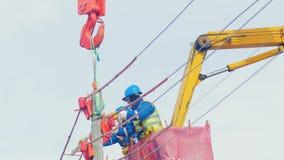 Οι υπάλληλοι εγκαθιστούν την κατασκευή στον ηλεκτρικό πόλο φιλμ μικρού μήκους