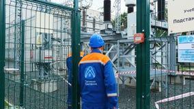 Οι υπάλληλοι με τη σκάλα μπαίνουν σε τον ηλεκτρικό σταθμό μετασχηματιστών φιλμ μικρού μήκους