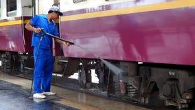 Οι υπάλληλοι ποτίζουν τη μάνικα ένα επιβατικό αυτοκίνητο σιδηροδρόμων φιλμ μικρού μήκους