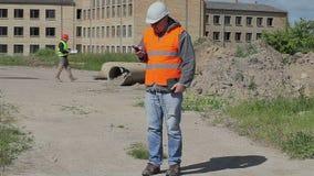 Οι υπάλληλοι κατασκευής με το κύτταρο τηλεφωνούν και έγγραφα απόθεμα βίντεο