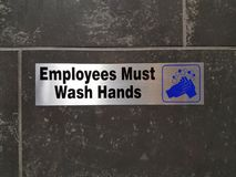 Οι υπάλληλοι πρέπει να πλύνουν το σημάδι χεριών στον τοίχο λουτρών Στοκ Εικόνες