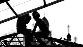 Οι υψηλός-οικοδόμοι εργαζομένων χτίζουν μια στέγη Στοκ Εικόνες