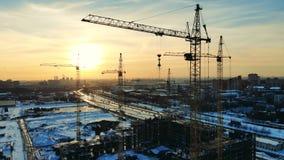 Οι υψωμένος γερανοί στέκονται στο εργοτάξιο οικοδομής απόθεμα βίντεο