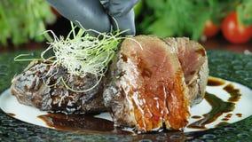 Οι φέτες βόειου κρέατος με το μέσο ψητό διακοσμούν με τα πράσινα στην κινηματογράφηση σε πρώτο πλάνο πιάτων φιλμ μικρού μήκους