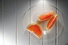 Οι φέτες του γκρέιπφρουτ βρίσκονται σε ένα διαφανές πιάτο σε έναν ξύλινο στοκ φωτογραφία με δικαίωμα ελεύθερης χρήσης