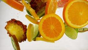 Οι φέτες Multifruit των διαφορετικών φρούτων περιέρχονται στο νερό με τους παφλασμούς και τις φυσαλίδες, σε αργή κίνηση κινηματογ απόθεμα βίντεο