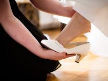 Οι φίλες γαμήλιων προετοιμασιών της νύφης την βοηθούν στα παπούτσια γάμου παπουτσιών μου Στοκ φωτογραφίες με δικαίωμα ελεύθερης χρήσης