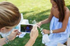 Οι φίλες παίρνουν τις φωτογραφίες στο τηλέφωνο στο τηλέφωνο προετοιμαμένος για ένα πικ-νίκ στοκ εικόνες με δικαίωμα ελεύθερης χρήσης