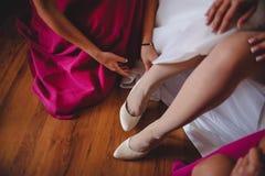 οι φίλες στα ρόδινα φορέματα, βοηθούν τα άσπρα παπούτσια ένδυσης νυφών στοκ φωτογραφία με δικαίωμα ελεύθερης χρήσης