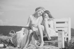 Οι φίλες στηρίζονται δύο κορίτσια που κάθονται στον πάγκο στο σανό Στοκ εικόνες με δικαίωμα ελεύθερης χρήσης