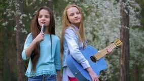 Οι φίλες Hipster μικρών παιδιών τραγουδούν τα τραγούδια και το χορό κιθάρα μαζί παιχνιδιού έχετε το δάσος διασκέδασης την άνοιξη απόθεμα βίντεο